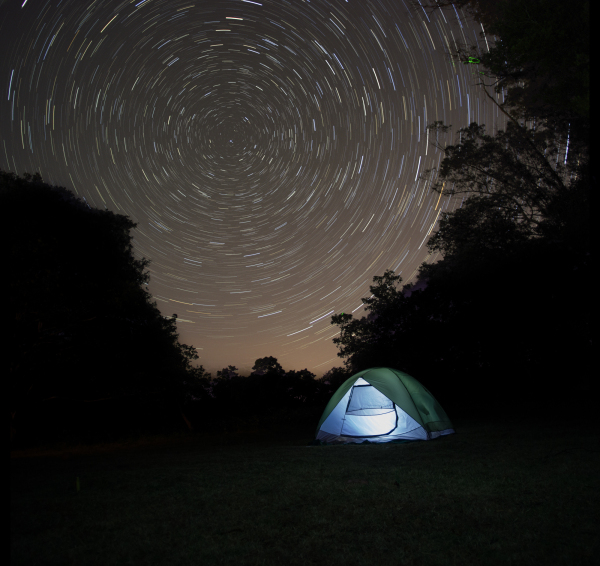 long exposure of star trails at night with tent