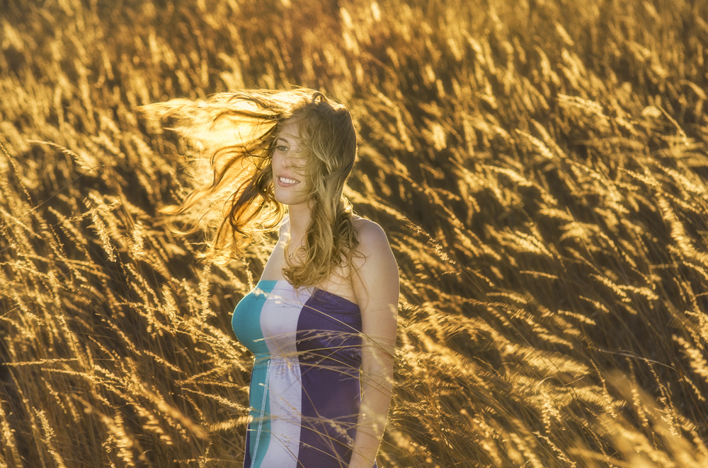 portrait of wind blown hair in a field at sunset