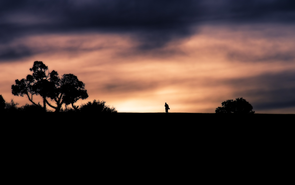 silhouette of skateboarder on mountain