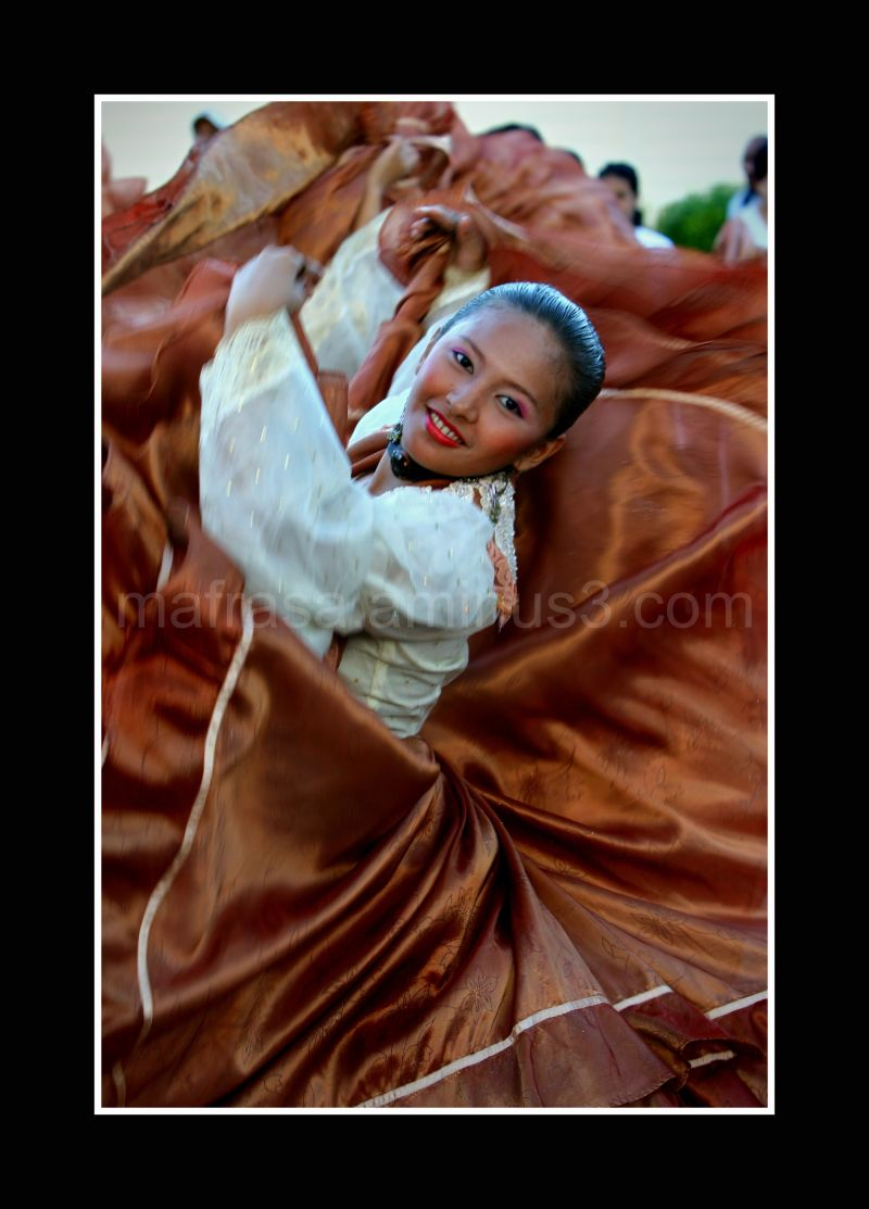 Young Filipina girl swirls her skirt in a dance