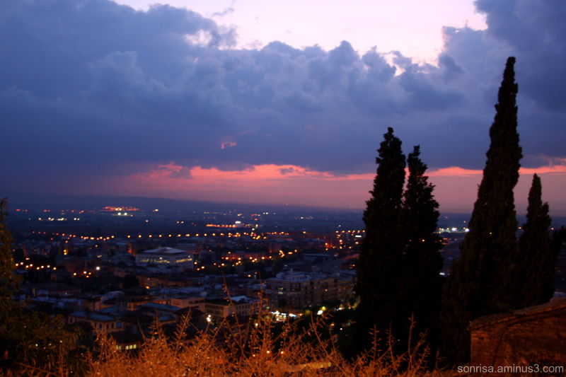 The city lights go on as the sun goes down.