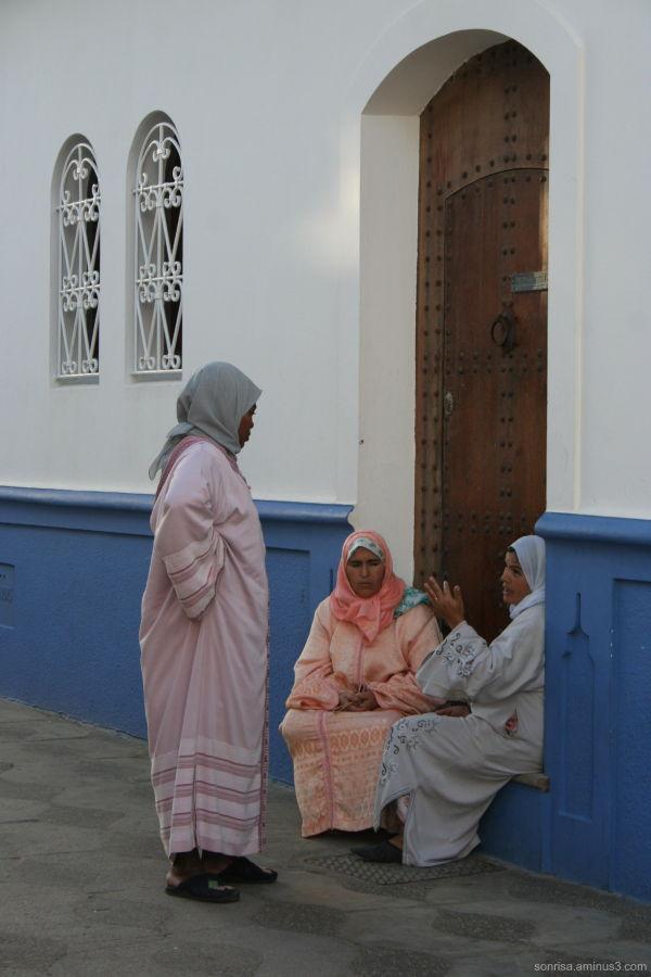 Women talking in a doorway.