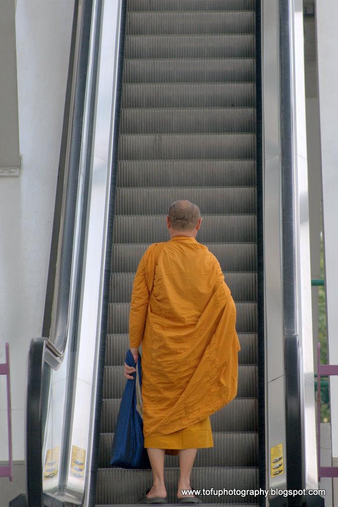 A monk on an escalator