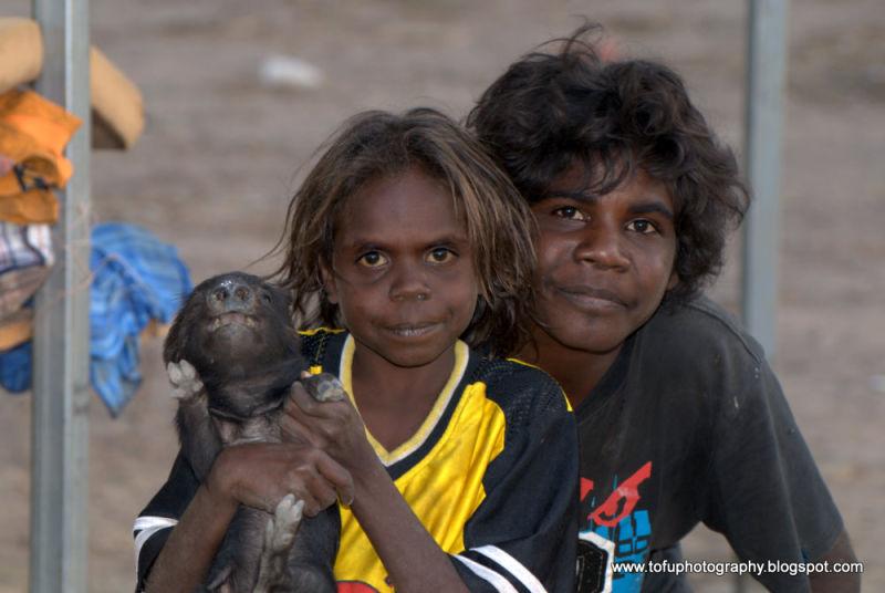 Kids holding a piglet