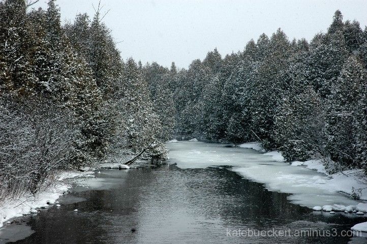 Snow falling by the river