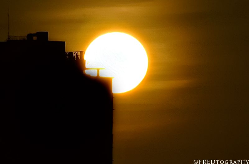 A sun rises against a building.