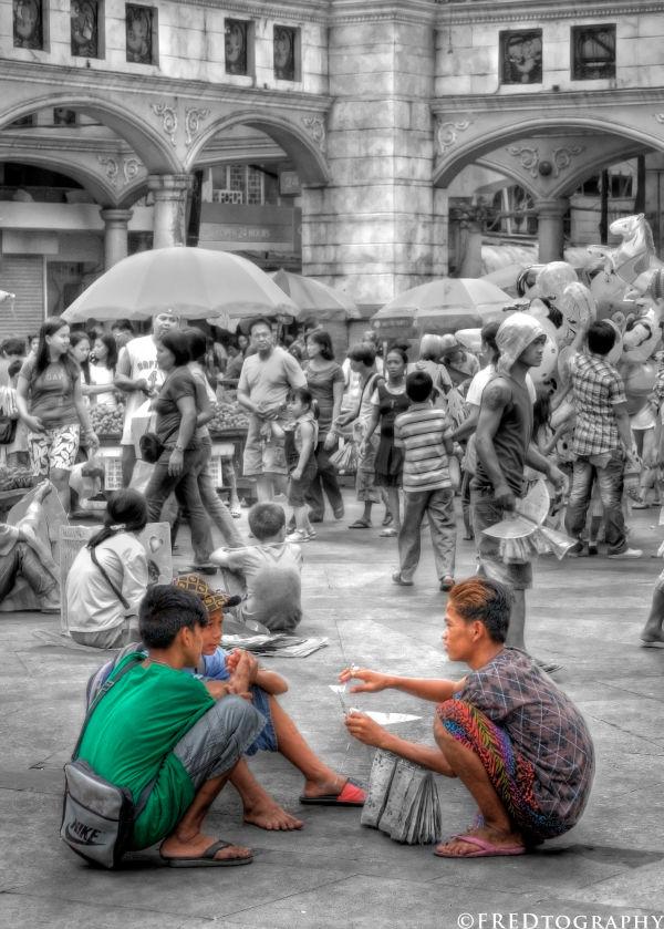 Kid vendors sitting down on the street.