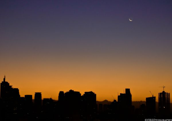 A crescent moon over Makati during twilight.