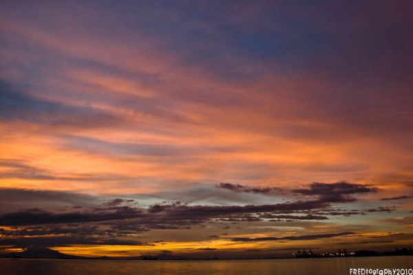 Wild colors appear on manila bay as the sun sets.