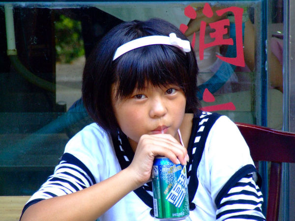 A young girl sips soda.