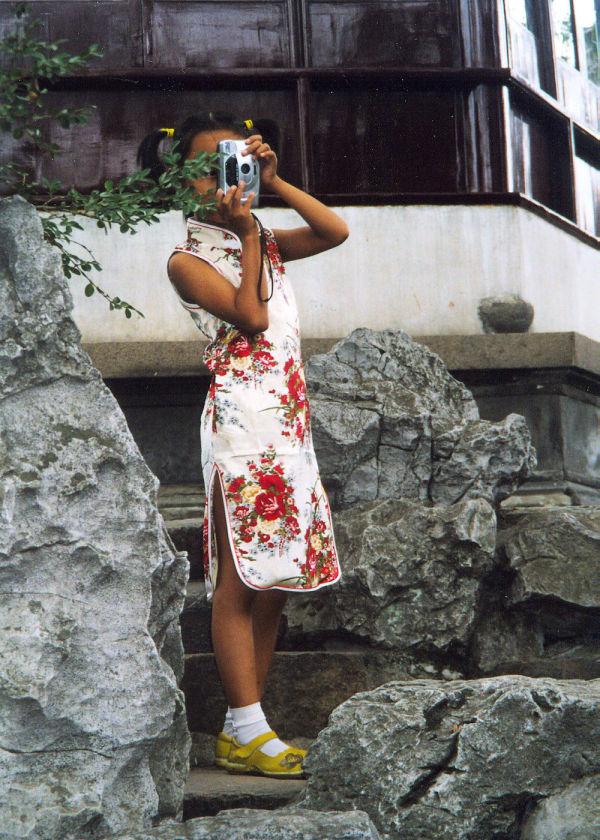 A young girl takes a photo in a Suzhou garden.