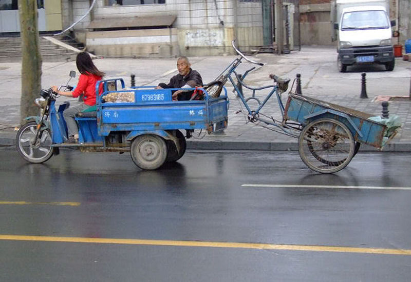 A man tows his friend's trike after a breakdown