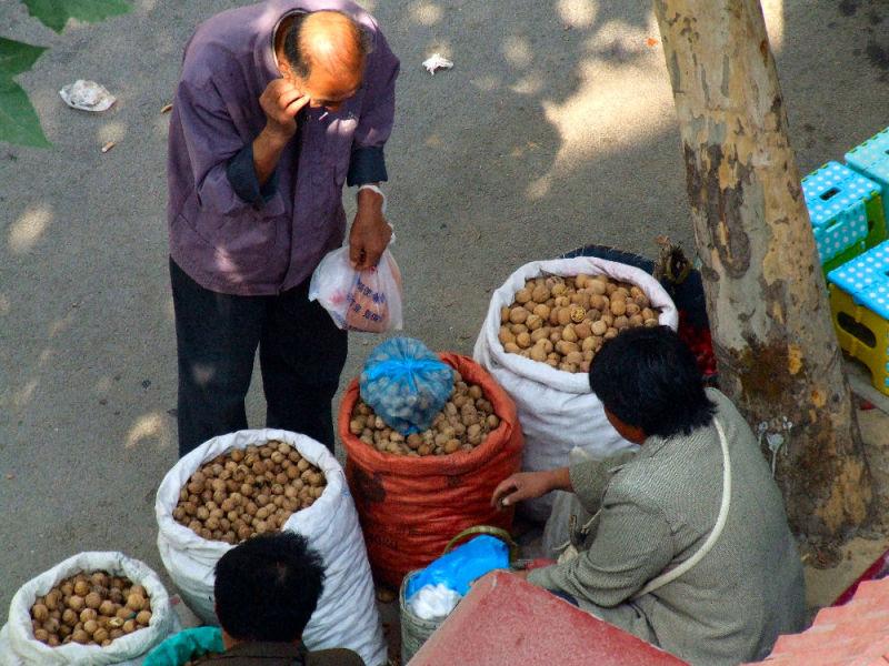 A man buys walnuts at a street market
