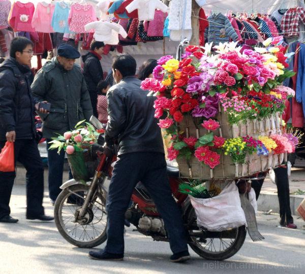 A man sells fake flowers at a market