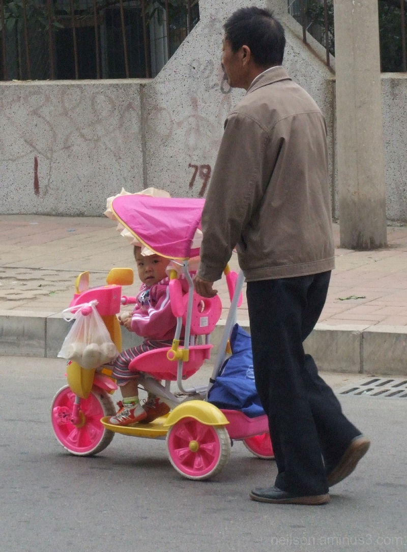 Grandfather pushes a baby stroller