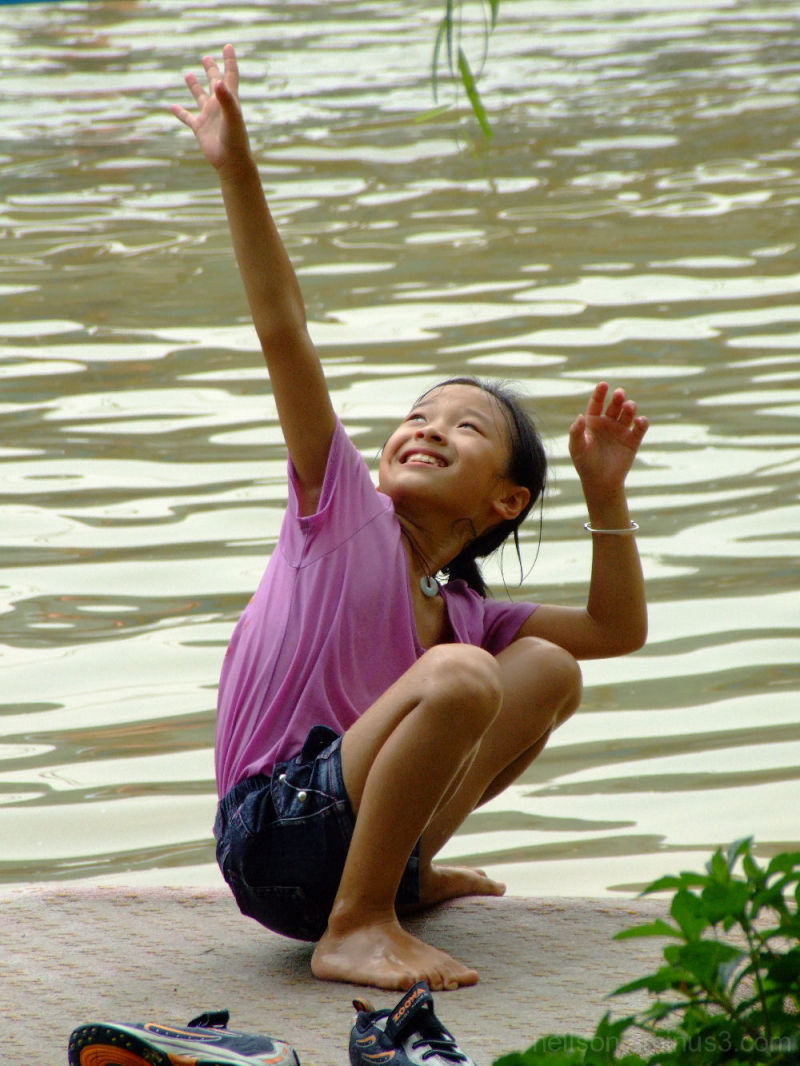A young girl tries to catch a rope swing.