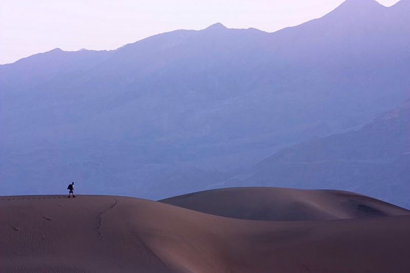 A hiker in the death valley dunes at sunrise