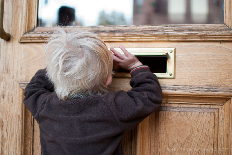 boy looking through mail slot