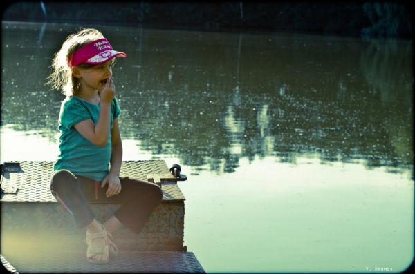 little girl sitting on a dam lid