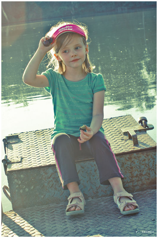 little girl sitting on the dam lid eating a prune