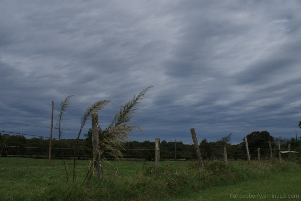 ominous clouds in sky with farm fence