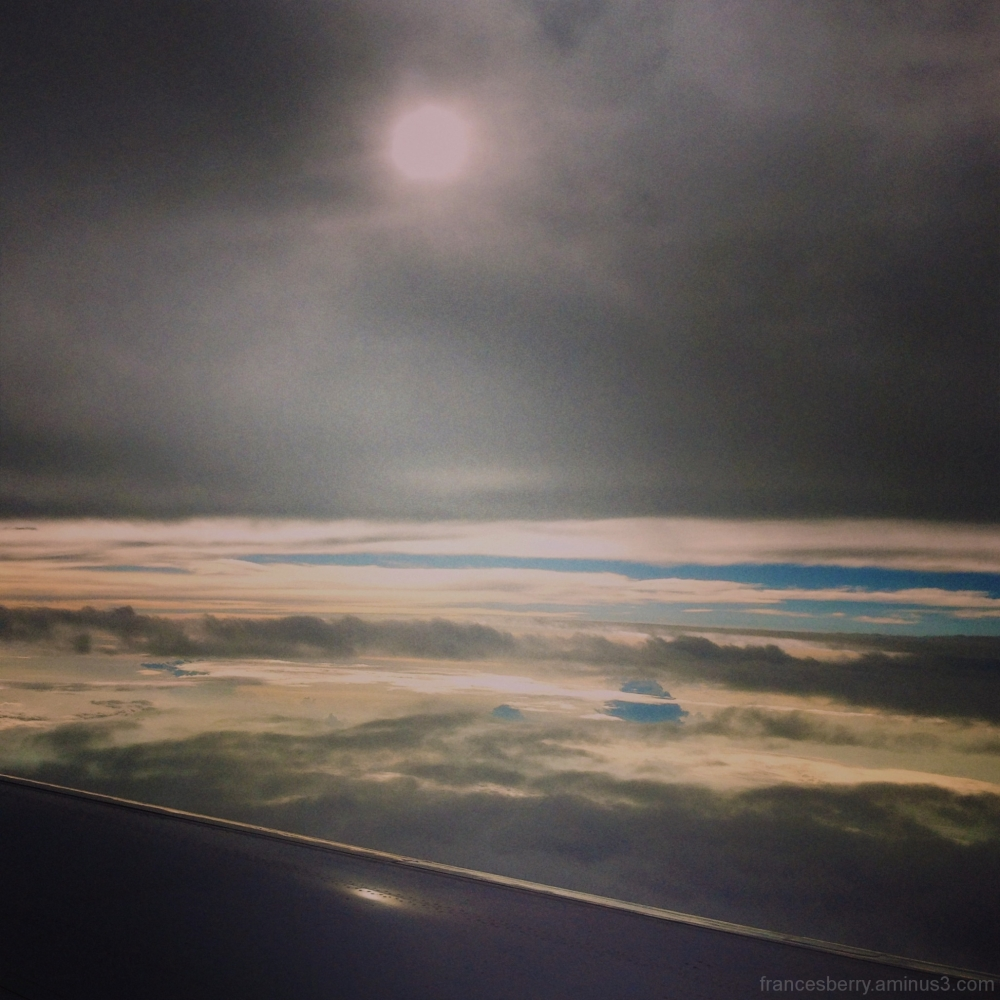 from the window of an airplane with clouds sun