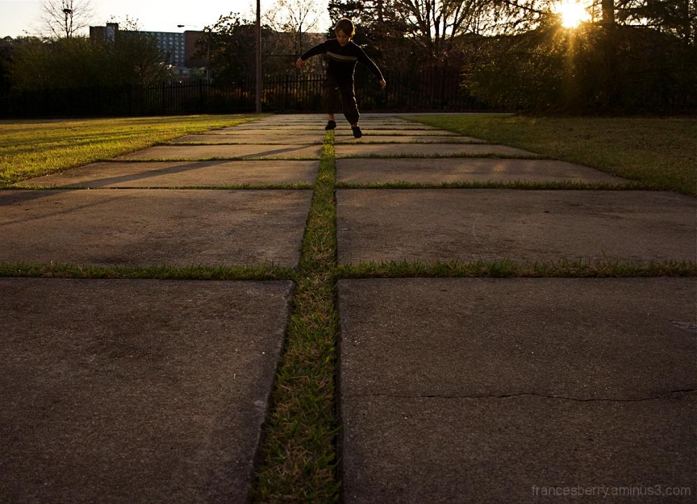 boy playing hopscotch on sidewalk of grass