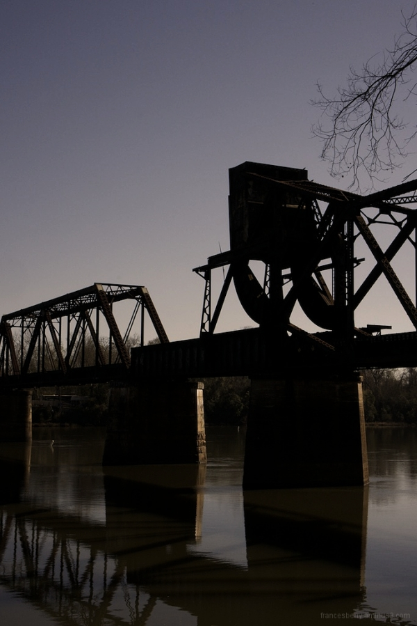 silhouette of an old railroad bridge over a river