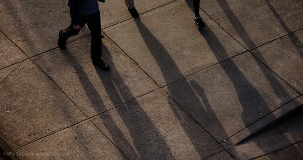 cut frame of feet walking on downtown sidewalk