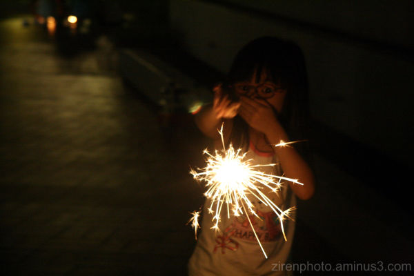 A girl playing around with sparklers.