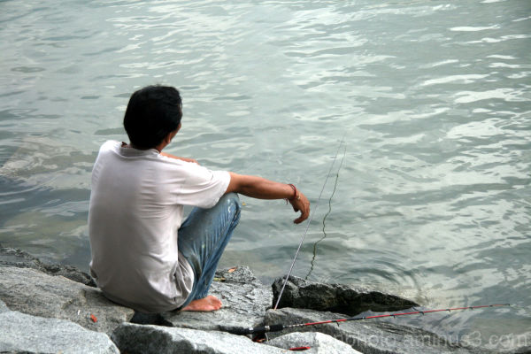 Desperate man waiting for fish to fall to his trap