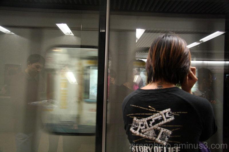 A tatoo-ed man waiting for the train.