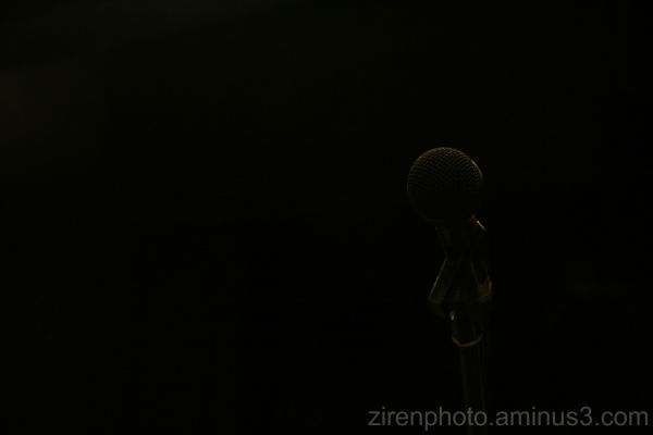 A dark outline of a microphone in an auditorium.