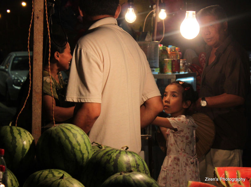 A young girl amazed by the fruit seller and fruits