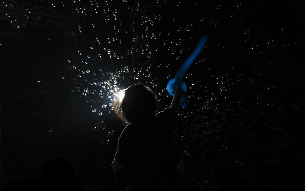 A young child admiring bubbles in Night Festival.