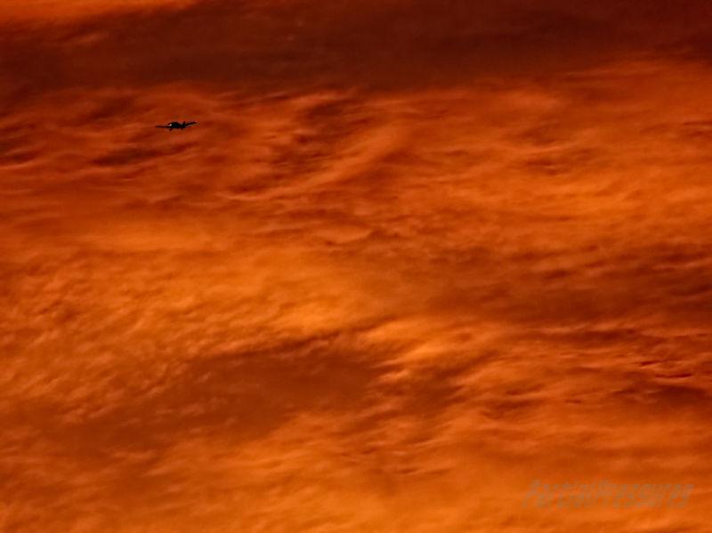 Light aircraft and sunset-lit clouds