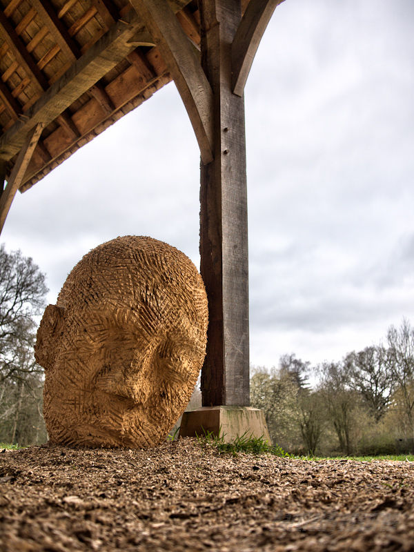 A carved head rests against an oak beam