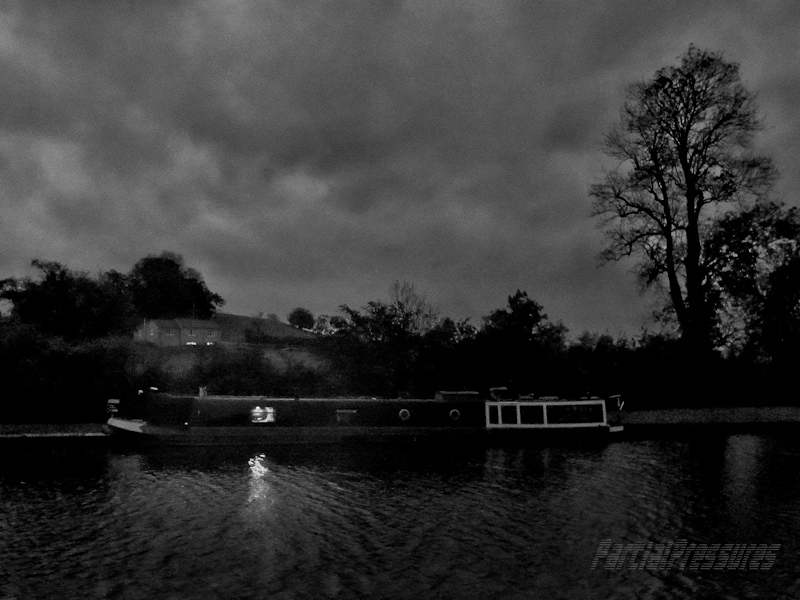 Narrowboat moored on the canal at night