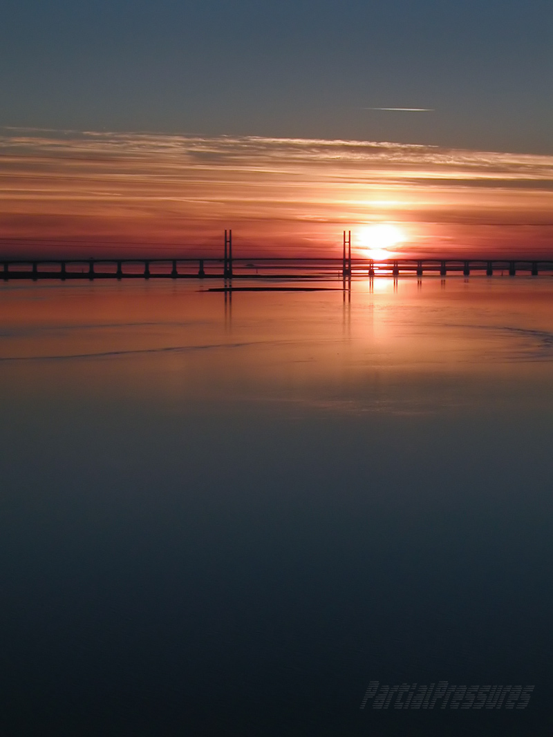 bridge at sunset floating between sky and water