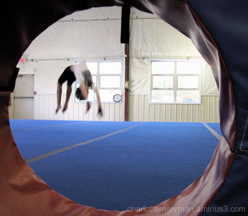 gymnast midair in back handspring with clock