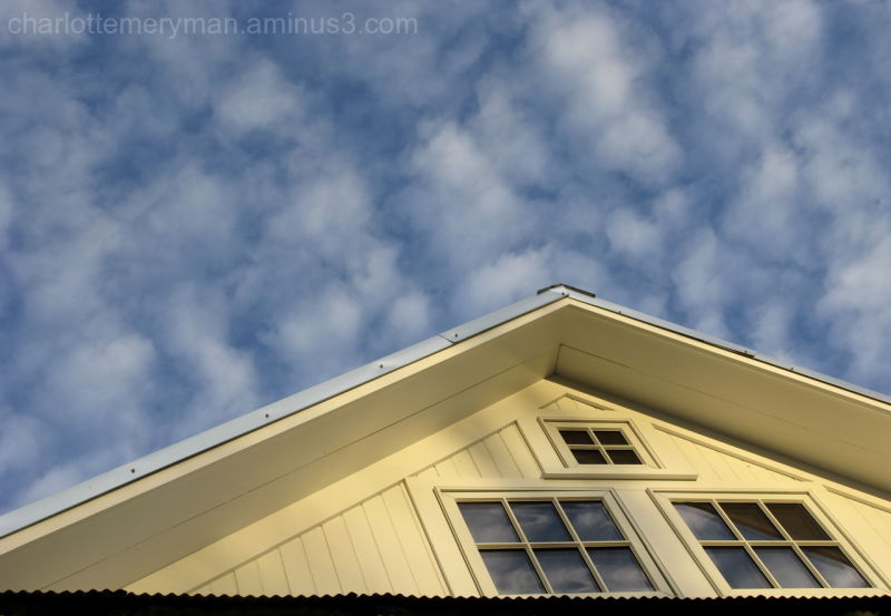 clouds reflected in windows of barn gable