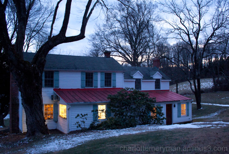 windows glow at dusk in a maryland farmhouse