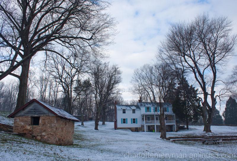 vista with stone springhouse, farmhouse in snow