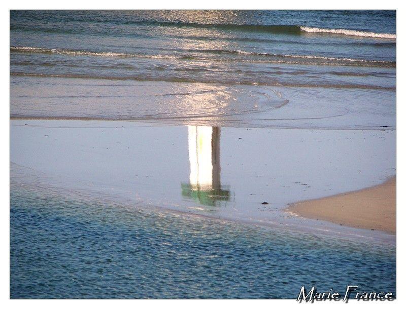 Reflet d'un phare sur sable et eau