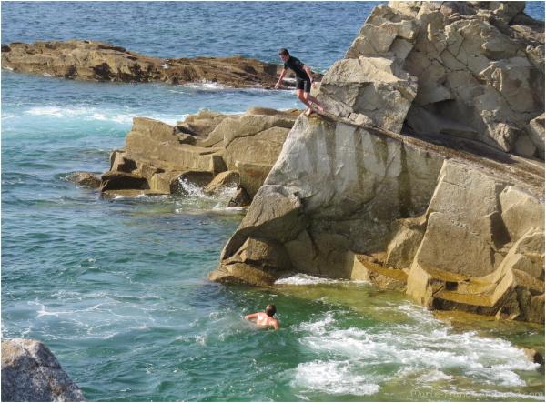 un adolescent saute des rochers dans l'eau