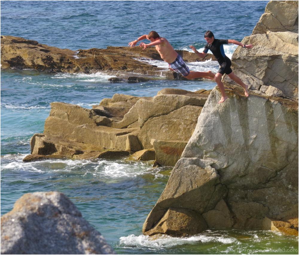 Deux adolescents sautent des rochersdans l'eau