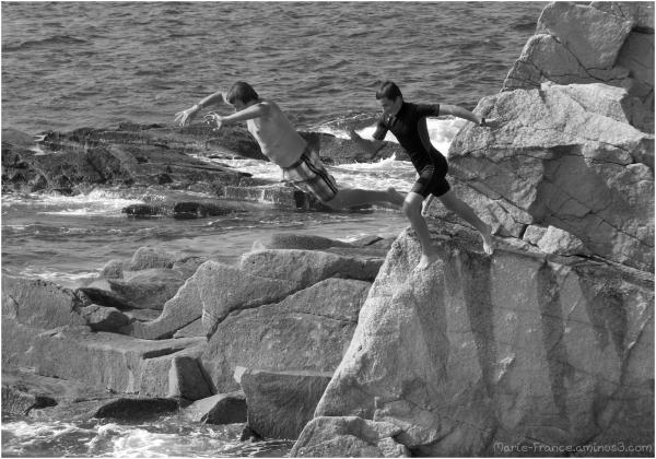Deux adolescents sautent des rochers dans l'eau