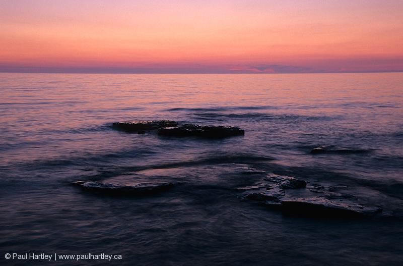 sunset over shorline rocks lake huron ontario