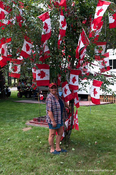 Woman in front of tree decorated with Canada Flags