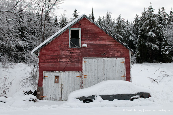 old red garage with snow cover car in winter
